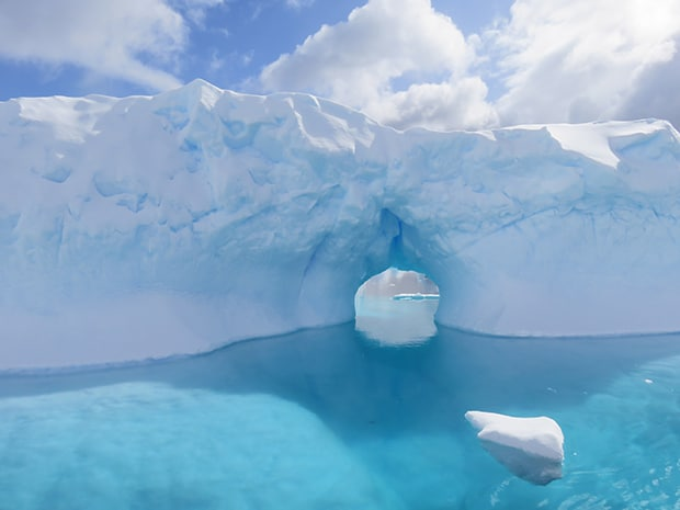 Bright blue ocean water in Antarctica and iceberg with an arch