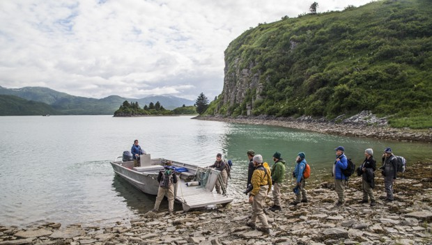 Guests from small ship cruise get on a skiff excursion from the shore in Alaska.