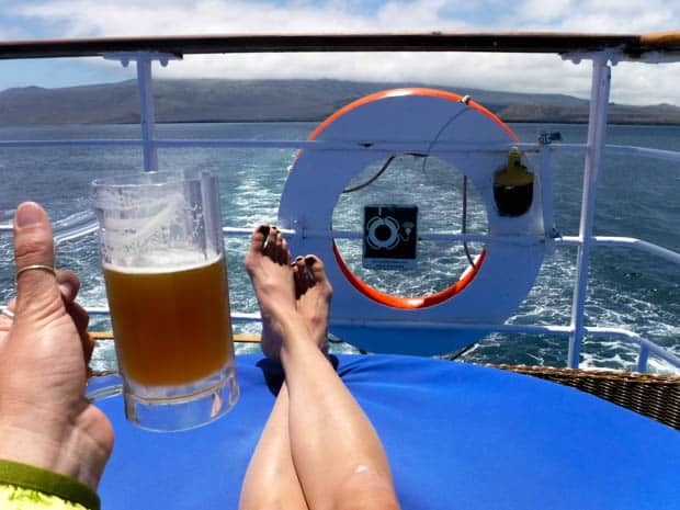 Stern of the boat with a happy traveler lounging on a chair enjoying a beer while the Galapagos Legend sails away from a Galapagos Island.
