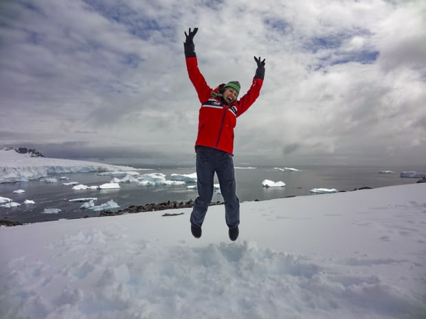 A solo woman traveler to Antarctica jumping on the snow with icebergs floating behind her.
