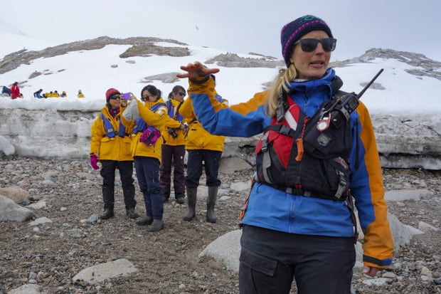 A woman guide explaining something to a group of Antarctica travelers.