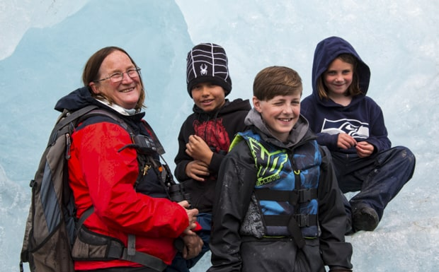 A woman guide in Alaska with a group of smiling kids sitting on an iceberg.