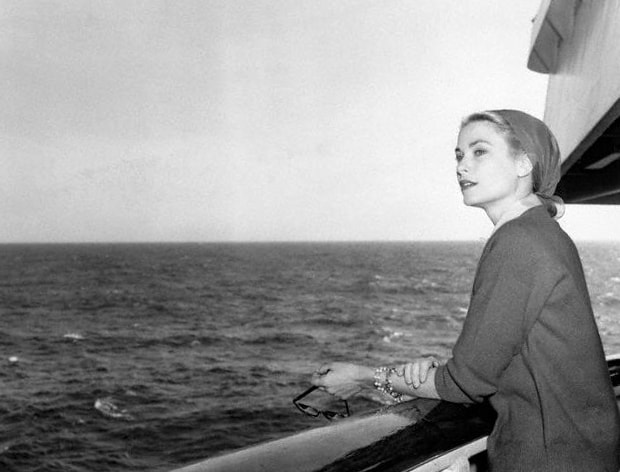 A black and white photo of Princess Grace aboard the Grace motor yacht, standing on the deck looking out over the ocean.