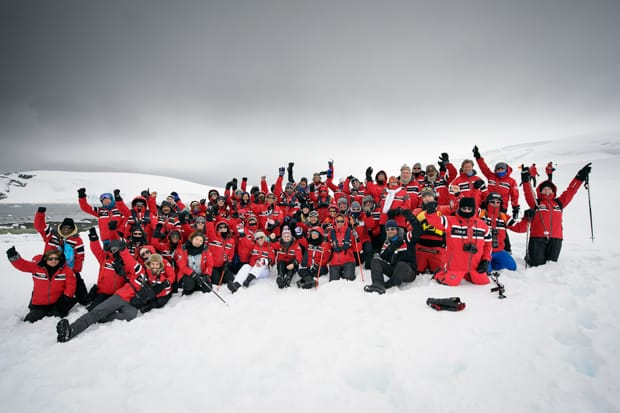 Group from a small cruise ship in Antarctica wearing their red polar expedition parkas on the snow.