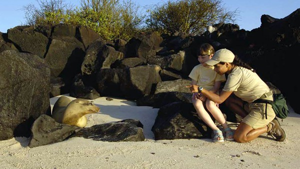 Galapagos naturalist talking to a young girl about a sea lion.