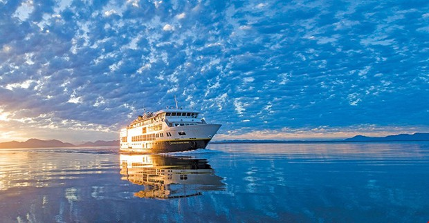 National Geographic Venture small ship first setting sail in 2019 with cloudy sky at sunset