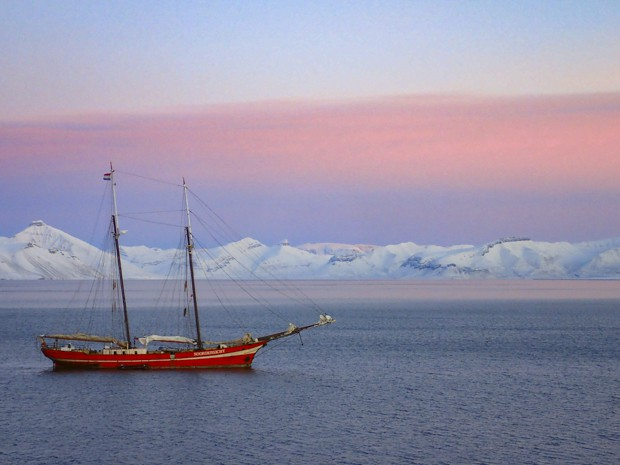 A sailing ship in Norway at sunset with snow-capped mountains