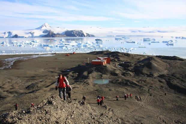 Small ship cruise guests hiking on Antarctica near a research station with icebergs in the background.
