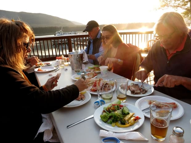 Guests from a small ship cruise in Alaska eating a seafood dinner at Orca Point Lodge along the water during sunset.
