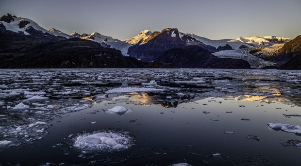 Floating ice below snow covered mountains in Patagonia.