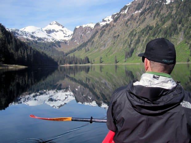 A man kayaking on still water in Alaska.