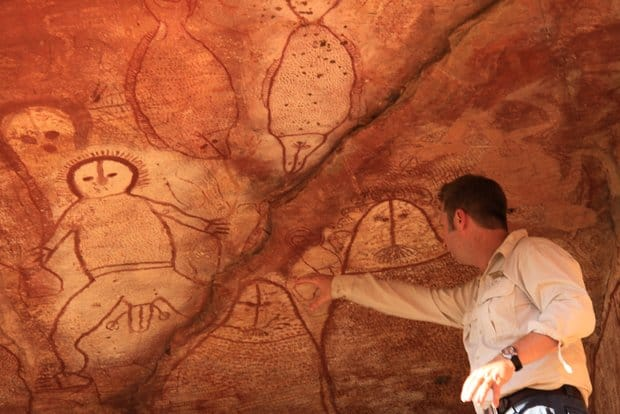 An Australian guide pointing at artwork inside of a cave in the Kimberley