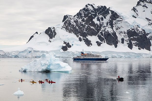 Group of kayakers, an iceberg and a skiff in front of a small ship in Antarctica