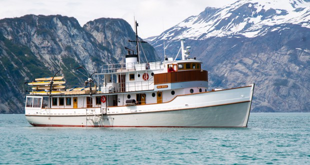 Small ship Sea Wolf cruise with mountains in the background sailing in Alaska.
