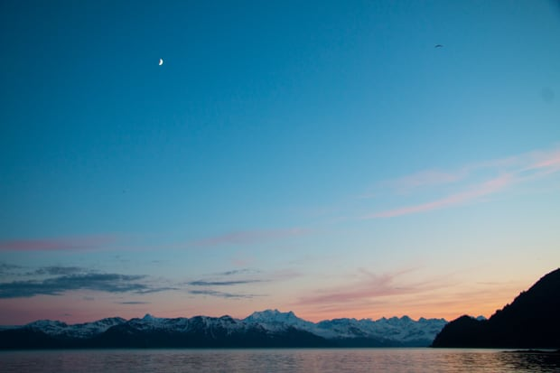Moon above the mountains in Alaska during sunset as seen from a small ship.