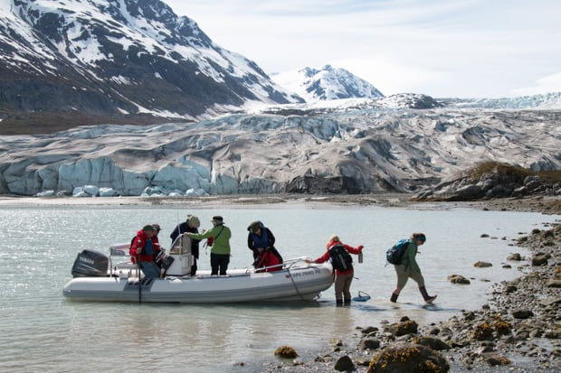 Guests on a skiff excursion from their small ship to the shore in Alaska to walk by the glacier.