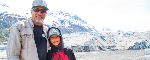 Founder Todd Smith and son posing in front of a glacier from their small ship cruise to Alaska.