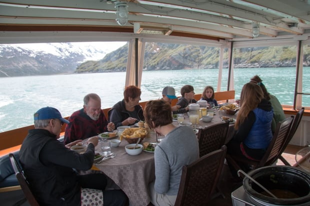 Guests eating dinner aboard the Sea Wolf surrounded by windows while scenic cruising in Alaska.