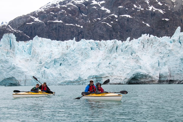 Guests from a  small ship cruise in double kayaks paddling in front of a glacier in Alaska.