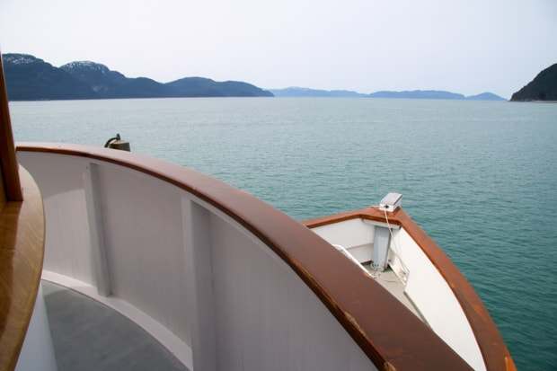 View from a deck looking down onto the bow of a small ship cruise in Alaska.