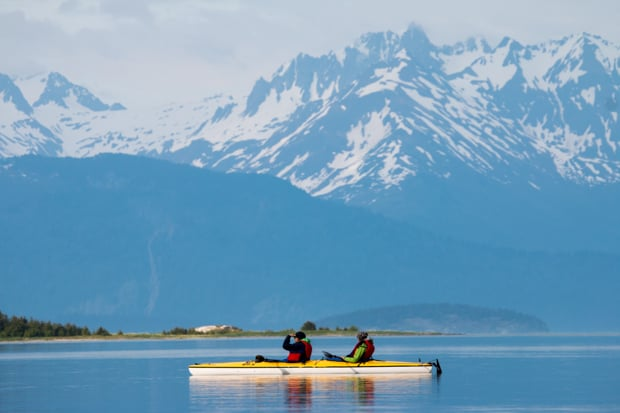 Guests from a small ship cruise  in Alaska kayaking with mountain peaks in the background.