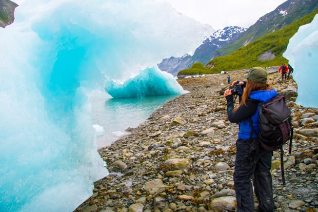 Guests on a small ship cruise tour taking pictures of bright blue ice bergs near the shore in Alaska.