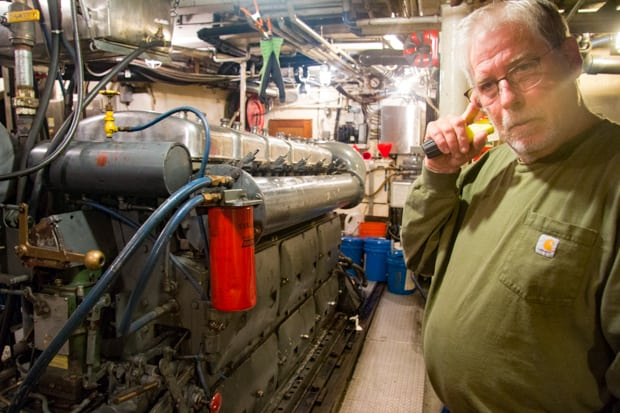 Engine room and crew member aboard the small ship Sea Wolf.