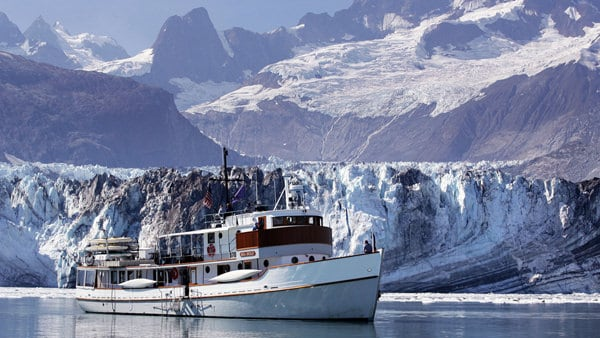 An Alaska small ship, the Sea Wolf, floats in front of a jagged white and grey glacier, beyond them, a sweeping purple hued Alaska mountain scape.