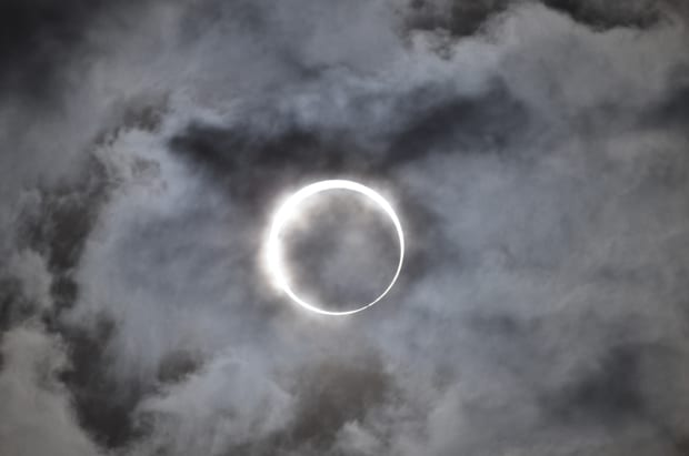 View of solar eclipse with light clouds.