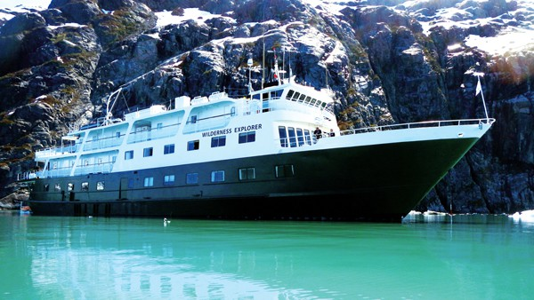 An Alaska small ship, the white and green wilderness explorer floats in teal waters against a rocky mountain side.
