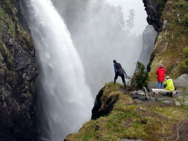 Three people standing near a cliff edge across from a raging waterfall in Alaska.