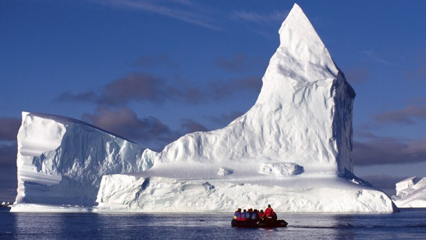 Small ship guests on a skiff excursion in front of huge unique shaped glaciers in Antarctica.