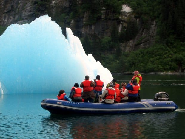 A group of people in a zodiac looking at a large piece of floating glacial ice in Alaska.