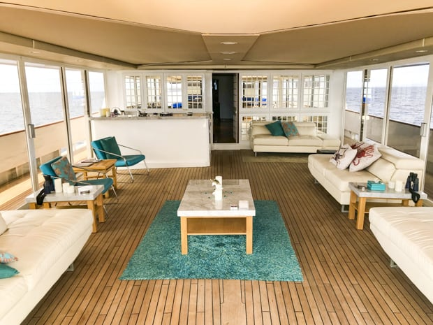Deck view of a enclosed outdoor lounge area with couches and chairs and a bar.  Large windows and sliding glass doors access the deck.