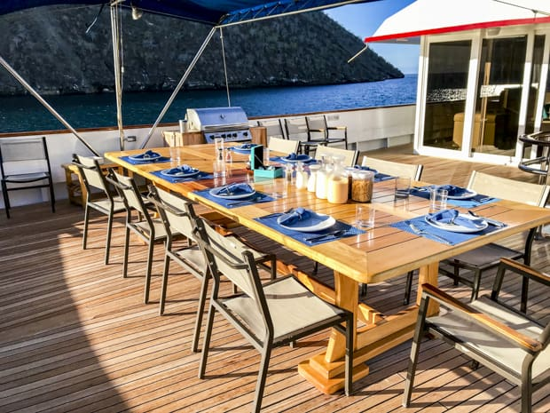 A guest table set for dining on the deck of the small ship cruise Passion on a sunny day while anchored off the coastline in the Galapagos.