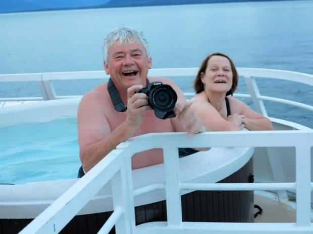 Happy guests in the hot tub on their small ship cruise in Alaska taking pictures of the scenery as they sail.
