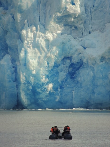 Guests on a skiff excursion from their small ship cruise in Alaska getting up close to a glacier.