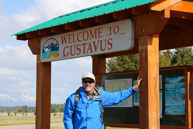 Adventuresmith founder Todd Smith standing in front of Welcome to Gustavus sign in Alaska.