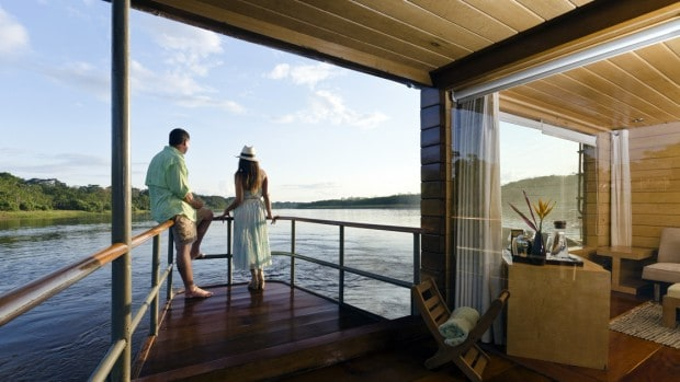 Couple on Amazon small ship cruise deck leaning on railing