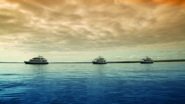 Three Galapagos small ships at anchor in a calm bay