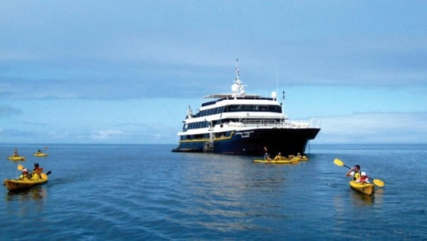 A Galapagos small ship with six kayakers paddling in the ocean in front of it.