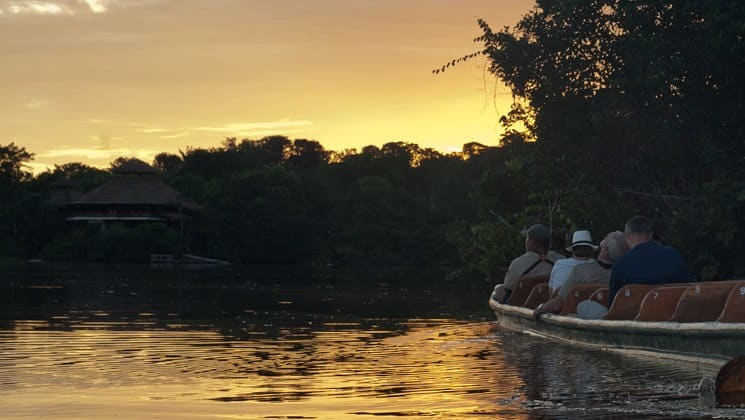 Sunset on the Amazon in Ecuador with group on skiff approaching jungle lodge