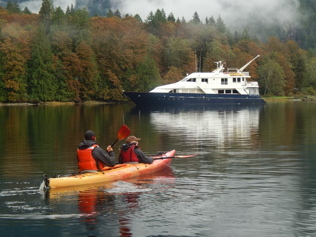 The Safari Quest yacht sails along the turning fall leaves of a San Juan Islands shoreline with two kayakers paddling toward the ship.