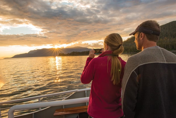 On a San Juan Islands cruise two guests stand onboard with a camera facing the sun setting over an island in the distance.