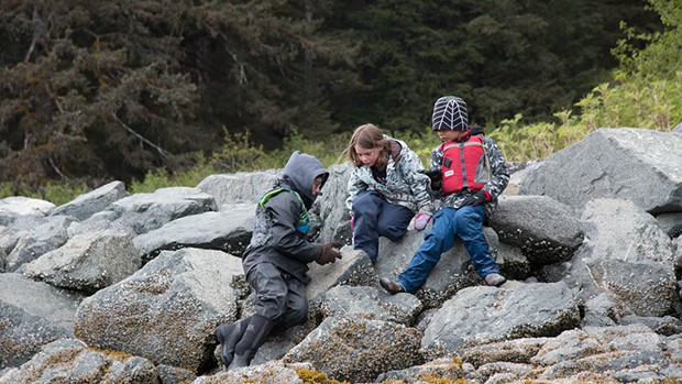 Three children talk amongs themselves as they sit on top of rocks on a shore excursion during their family friendly Alaska small ship cruise,