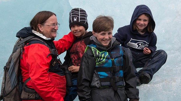 A family of 4 smile and pose as they sit on top of icebergs during their family Alaska small ship cruise.