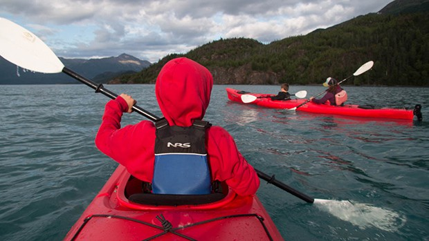 A cloudy day, in a body of water surrounded by forested hillsides, children and their parents enjoy kayaking in red double kayaks during their active family friendly Alaska small ship cruise,