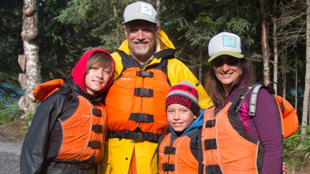 a happy family of four pause in their orange life jackets for a photo opportunity while aboard an Alaska small ship cruise.