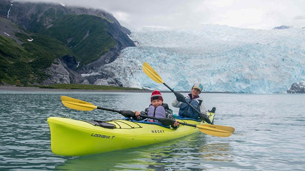 During an Alaska small ship cruise activity, two guests paddle in a lime green kayak in front of a massive white and teal glacier.