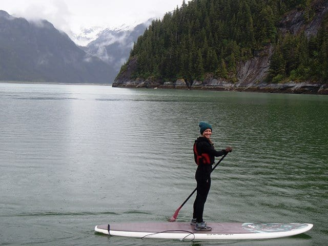 Happy guest stand up paddle boarding in calm waters from a small ship cruise in Alaska.